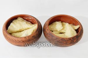 Глиняные горшочки смазываем сливочным маслом, выкладываем в них вареники.