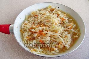 Выложить рёбрышки в миску и накрыть крышкой. В мясной сок, оставшийся на сковороде, добавить 35 мл масла, выложить квашеную капусту и залить её 1 стаканом бульона.