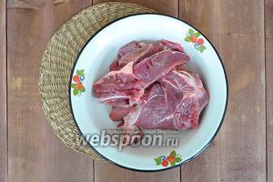 Мясо нарезать, крупные косточки порубить, чтобы они помещались в тажин.