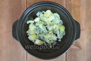 В тажин положить кусочек сливочного масла и 3 столовых ложки оливкового, разогреть и добавить нарезанный лук, жарить до прозрачности.