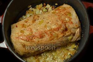 Кладем  к луку и чесноку свинину целым куском, постоянно поворачиваем, чтобы мясо зарумянилось. Если лук начнет сильно зажариваться, ничего страшного, будет только вкуснее, однако, нужно следить, чтобы лук не превратился в угольки.