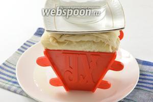 Завернуть края марли наверх. Установить сверху небольшое блюдце, а на него — груз(пол-литровая банка с водой). Поставить пасху в холодильник минимум на 12 часов, периодически сливая образовавшуюся жидкость.