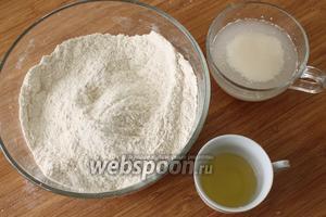 Развести в половине стакана тёплой воды дрожжи с сахаром, подождать пока появится характерная «шапочка». В муку положить соль и перемешать, в середине сделать углубление и влить туда дрожжи. Затем  добавив тёплую воду, замесить мягкое, но не прилипающее к рукам тесто. В конце замеса добавить масло.