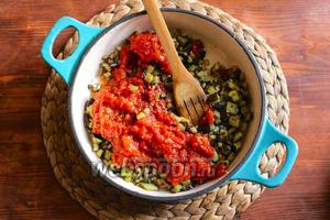 Переложите обжаренные баклажаны в соусник или глубокую сковороду и добавьте рубленные и очищенные томаты, выдавите через пресс 3 зубчика чеснока, приправьте чёрным перцем и влейте томатный сок из банки.
