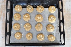 Выложить тесто на лист, мокрыми руками формируя шарики, а потом их расплющить. Присыпать овсяными хлопьями. Выпекать при 180ºC минут 15-17.