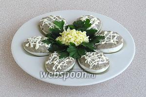 Фаршированные яйца разложить на специальном блюде, а если его нет, то и на обычной тарелке. Украсить яйца сеточкой из майонеза, зеленью петрушки и натёртым желтком.