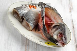 Рыбу почистить, выпотрошить (очень аккуратно удалить жёлчный пузырь, чтобы не испортить вкус рыбы), удалить жабры, глаза. Тонким ножом срезать филе. Вымыть под холодной водой филе и хребет с головой. Филе сибаса накрыть пищевой плёнкой и убрать в холодильник.