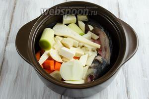 К кастрюлю выложить хребет рыбы с головой, подготовленные овощи.
