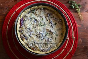 Залейте получившейся жидкой начинкой киш и немного распределите её среди лука пальцами. Присыпьте пирог оставшимся тёртым сыром и отправьте в духовку на 50-60 минут, или до тех пор пока начинка не станет пышной и немного не поднимется, а сыр не покроется золотистой корочкой.