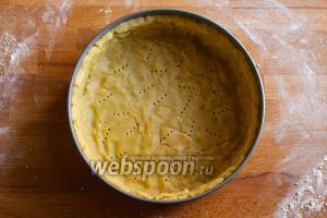 Смажьте сливочным маслом разъёмную форму диаметром 21 см и выстелите её пергаментом. Можете просо перенести пласт песочного теста в форму и бережно распределить его, срезав излишки, но мне нравятся неровные края, так что я отрываю по кусочку раскатанного теста и формирую сначала дно, а затем стенки пальцами. В итоге получается очень аутентичный пирог с живописной песочной основой. Наколите дно пирог вилкой и отправьте прямо в форме в морозильную камеру на 15 минут. Это очень важный момент, если вы провозились с тестом и масло в нём успело нагреться, песочная основа может получится жесткой. Но когда мы отправляем её в морозильную камеру, масло достаточно охлаждается и у вас получится очень рассыпчатая хрустящая основа для пирога!