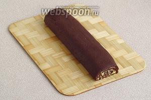 Аккуратно отсоединяя бумагу, закрутить шоколадный пласт с кремом в рулет и отправить его в морозилку на 40 минут.