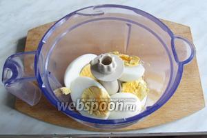 Вареные яйца разрезать пополам и положить в чашу измельчителя блендера.