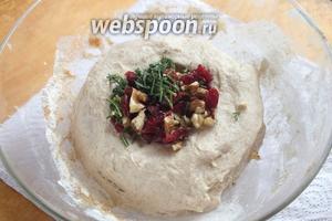 В подошедшее тесто добавьте нарубленные листья розмарина, измельчённые орехи и клюкву.