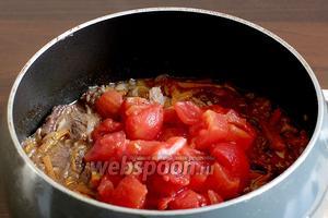 Помидоры с соком добавить к мясу, когда оно будет уже мягким. Закрыть снова крышкой и потомить всё вместе ещё 5-7 минут.