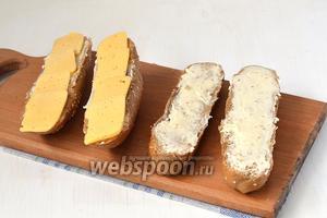 На половину смазанных багетов выложить тонко порезанный твёрдый сыр.