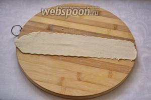 Из колбаски раскатайте пласт. Неровный край можно подрезать. Доску или стол лучше припудрить мукой, чтоб тесто не липло. Верхнюю часть теста смазать растительным маслом (при помощи кисточки). Края теста смазывать маслом не надо, иначе тесто не склеится.
