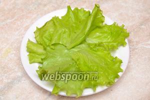 Укладываем на тарелку листья салата.