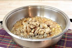 К луку, доведённому до полуготовности, добавить размороженные белые грибы. Жарить, помешивая, 3-4 минуты.