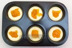 Форму для кексов смажем маслом. Выкладываем 1-2 ст.л. теста, на тесто — 1-2 ч.л. джема.