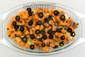 Поверх рыбы выкладываем нарезанные оливки, каперсы. Чуть присолим. Сильно не надо солить, потому что каперсы уже солёные.