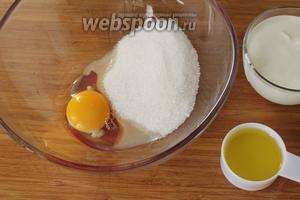 В отдельной миске взбить яйцо с сахаром до пышной пены, влить масло и сметану. Взбить ещё раз.
