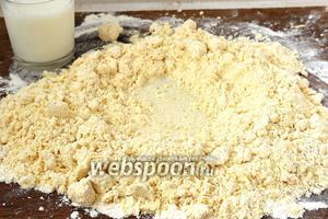 В середине крошек сделать углубление с бортиками и частями вливать молоко, замешивая тесто.
