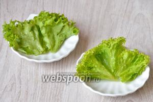 Раскладываем на тарелки промытые листья салата.