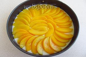 Персики вынуть из сиропа, нарезать тонкими дольками и выложить по поверхности застывшей начинки «чешуёй».