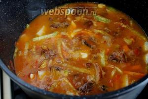 Добавить к обжарке подогретый бульон (у меня говяжий) или горячую воду (от холодной мясо дубеет). Довести до кипения, убавить огонь и тушить под крышкой около получаса — зависит от мяса.