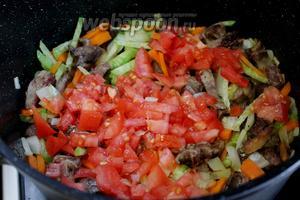 Добавить нарезанный помидор в казан к обжарке мяса с овощами.