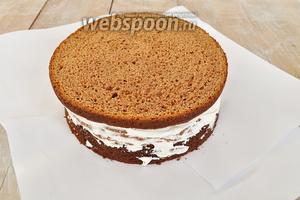 На тарелку для торта положить с трёх сторон листы бумаги, когда торт будет оформлен, их просто вытянуть и тарелка останется чистой. Нанести сливки на каждый корж.