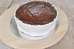 Нанести шоколад наверх торта, когда он остынет, выровнять бока торта кремом. Для этого удобнее использовать вращающуюся подставку.