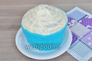 Нижнюю часть торта под мастику смазать тонким слоем сгущённого молока кисточкой и дать впитаться. Наложить мастику и разровнять руками, прижимая к торту, подрезать всё не нужное ножом.