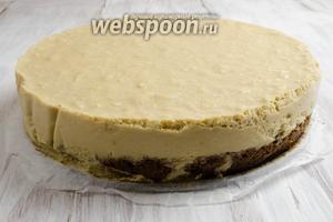 Торт аккуратно освободить от формы, снять пергаментную полоску по бокам. Нарезать порционными кусками. Растопить шоколад на водяной бане. Украсить шоколадными нитями верхнюю поверхность. Подавать охлаждённым.