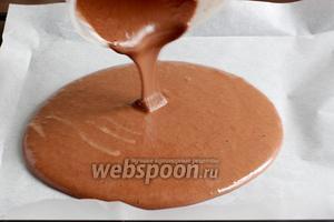 Вылить шоколадное тесто на противень, выложенный пергаментом, разровнять по краям.
