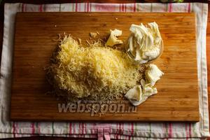 Сыр натрите на мелкой тёрке, а моцареллу разорвите на крупные волокна.