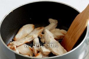 В сотейнике или воке хорошенько разогреть смесь кунжутного и подсолнечного масла. Обжарить курицу в течение 8 минут. Немного подсолить.