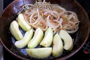 Сдвинуть лук на край, не переставая перемешивать при обжарке, уложить на свободное место дольки яблок.