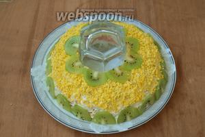 Поверх яблок нанести майонез и равномерно распределить его по поверхности. Посыпать верх салата желтками и украсить нарезанными киви. Перед подачей аккуратно извлечь стакан. Приятного аппетита!