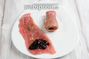 На край куска мяса выложить немного начинки. Скрутить рулетом. Закрепить (обвязать вокруг) с помощью кулинарной или обычной нити.