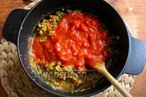 Добавьте в чечевицы консервированные рубленные помидоры и перемешайте. Увеличьте огонь и дайте жидкости снова закипеть.