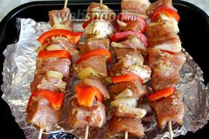 Нанизать на деревянные шпажки мясо, чередуя его с луком и перцем. Поместить над противнем (можно не застилать фольгой). Духовку нагреть на максимум, под гриль поставить противень на 10-15 минут.