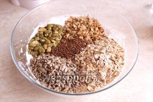 Всыпьте в белково-сахарную смесь орехи, хлопья и семена.