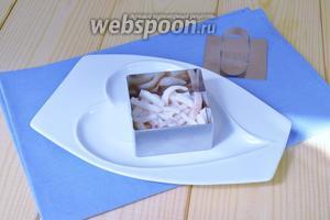 Приступаем к сборке салата. Установить форму на тарелке и первым слоем выложить кальмаров, уплотнить крышкой. Нанести немного заправки.