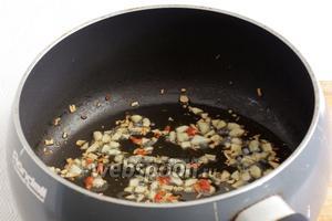 В разогретой смеси кунжутного и подсолнечного масла быстро обжарить чеснок и чили до появления запаха.