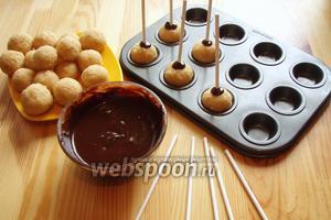 В каждый шарик вставляем палочку или шпажку предварительно окунув в шоколад и отправляем в холодильник до застывания основы на 15-20 минут.
