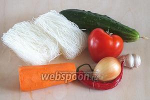 Подготовьте необходимые ингредиенты: фунчозу, свежий огурец, крупный помидор с плотной кожицей, морковь, перчик чили, луковицу, зубчики чеснока...