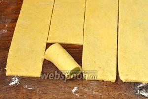 Выкладывать кусочки ревеня на полоски теста и заворачивать их в тесто. Края теста прижать для лучшего соединения.