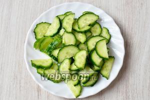 Сначала подготавливаем необходимые ингредиенты для салата. Нарезаем огурцы тонкими полукольцами.