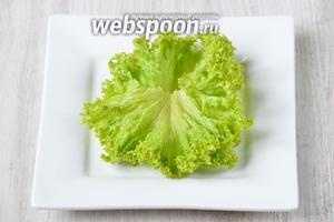 Раскладываем на тарелку листья салата.